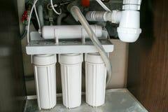 Sistema di depurazione delle acque di osmosi inversa a casa Installazione dei filtri da depurazione delle acque sotto il lavandin fotografie stock libere da diritti