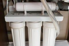 Sistema di depurazione delle acque di osmosi inversa a casa Installazione dei filtri da depurazione delle acque sotto il lavandin fotografie stock