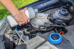 Sistema di raffreddamento di riempimento dell'automobile della mano con il liquido refrigerante fotografie stock