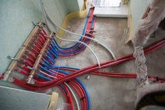 Sistema di riscaldamento radiante dell'installazione del riscaldamento di pavimento L'uomo installa la costruzione di pavimento s immagini stock