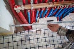Sistema di riscaldamento radiante dell'installazione del riscaldamento di pavimento L'uomo installa la costruzione di pavimento s fotografia stock libera da diritti