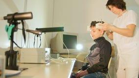 Sistema diagnostico del ` s dei bambini di salute - l'optometrista metta sopra l'attrezzatura dell'cervello-occhio per il pazient video d archivio