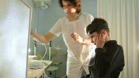 Sistema diagnostico del ` s dei bambini di salute - l'optometrista metta sopra l'attrezzatura dell'cervello-occhio per il pazient stock footage