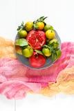 Sistema hermoso de las frutas granada, mandarina, pera en la materia textil rosada y fondo de madera blanco Fotografía de archivo