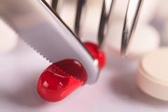 sistema médico de las píldoras, del cuchillo y de la bifurcación de cena de la comida con los cubiertos y las píldoras Imagen de archivo