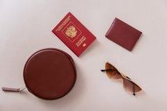 Sistema mínimo femenino del viaje Pasaporte marrón, titular de tarjeta y cartera con un bolso y vidrios en un fondo beige en colo foto de archivo