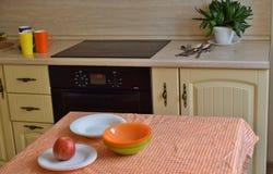 Sistema multicolor de platos de las placas, de las tazas, de las bifurcaciones, de las cucharas y de los cuchillos en la cocina e fotos de archivo libres de regalías