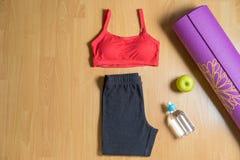 Sistema para el desgaste del deporte del ` s de las mujeres de la práctica de la yoga con la estera de la yoga, la botella de agu Fotografía de archivo libre de regalías