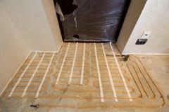 Sistema rojo de calefacción del alambre del cable eléctrico instalado en piso del cemento en pequeño nuevo sitio inacabado con la imagen de archivo