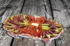 Sistema sabroso del plato del aperitivo en vieja superficie de madera agrietada anudada del Grunge de la mesa de picnic Fotos de archivo