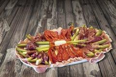 Sistema sabroso del plato del aperitivo en vieja superficie de madera agrietada anudada del Grunge de la mesa de picnic Imagen de archivo libre de regalías