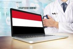 Sistema sanitario de Yemen en tema de la tecnología Bandera yemení en la pantalla de ordenador Doctor que se coloca con el esteto imagenes de archivo