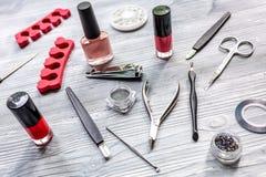 Sistema y esmalte de uñas de manicura para el tratamiento de las manos en fondo de madera Imágenes de archivo libres de regalías