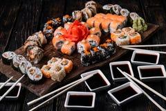 Sistema y palillos grandes del sushi en el fondo de madera fotografía de archivo