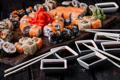 Sistema y palillos grandes del sushi en el fondo de madera fotografía de archivo libre de regalías