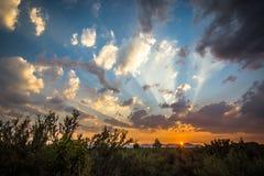Sistemas de The Sun detrás de las montañas en Oregon central Foto de archivo