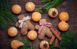 Sistemas del decaradio de la Navidad Pequeños hombres del pan de jengibre con las mandarinas, el canela y un anisetree Imágenes de archivo libres de regalías