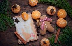 Sistemas del decaradio de la Navidad Pequeños hombres del pan de jengibre con las mandarinas, el canela y un anisetree Fotografía de archivo libre de regalías