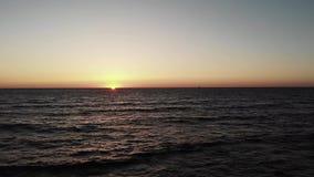 Sistemas rojos del sol sobre el mar del océano con las ondas con el pequeño barco negro del yate en horizonte Puesta del sol con  almacen de metraje de vídeo