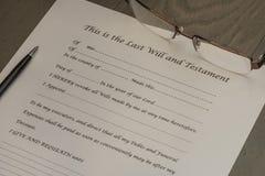 Sisten skallr och testamentdokumentet med ett par av exponeringsglas och pennan royaltyfria foton