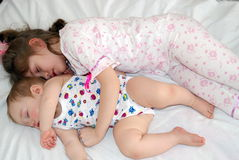 Sister and the brother. The seven-year girl in a pyjamas sleeps on a white bed-sheet having embraced the little boy Royalty Free Stock Image