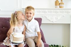 Sister brother birthday party. Cute little boy and beautiful girl are sitting on a chair together. Younger sister congratulates his older brother on his birthday stock photos