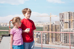 Sister, brother with camera standing on roof. Of high building Stock Photos