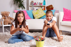Sister and brother compete for watching TV Royalty Free Stock Photos