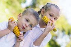 Sister and brother eating corn Stock Photos