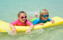 Sister and brother have fun with air mattress at the beach stock photography