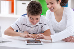 Sister and brother having fun with digital tablet Royalty Free Stock Images