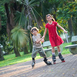 Sister and brother having fun rollerblading Stock Images
