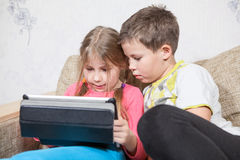 Sister and brother having fun with tablet pc while sitting on sofa together Royalty Free Stock Photography