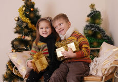 Sister and brother having fun under golden Christmas tree Stock Image