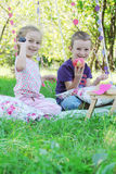 Sister and brother having funny picnic under trees Royalty Free Stock Image