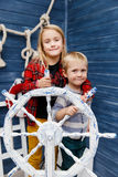 Sister with brother at helm Royalty Free Stock Images