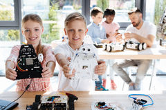 Sister and brother holding their robot models. Gifted teens. Happy smiling siblings standing near the working table during their robotics class and holding their Stock Photo