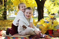 Sister and brother hugging under autumn tree Stock Photo