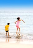 Sister and brother jumping on waves Royalty Free Stock Image