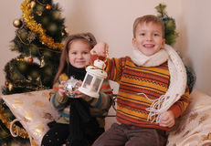 Sister and brother in knitted clothes under golden Christmas tre Stock Images