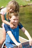 Sister and Brother Love. A young sister and brother at the lake, he's proudly holding his new wakeboard and she hugging him Stock Image