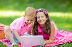 Sister and brother  lying down on blanket and using laptop Royalty Free Stock Photo