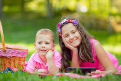 Sister and brother  lying down on blanket and using tablet Stock Photos