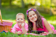Sister and brother  lying down on blanket and using tablet Royalty Free Stock Images