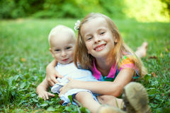 Sister and brother lying on green grass Stock Images