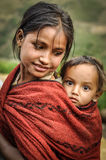 Sister and brother in Nepal. Dolpo, Nepal - circa June 2012: Brown-haired girl with piercing in her nose has her smaller brother with big brown eyes on back in royalty free stock images
