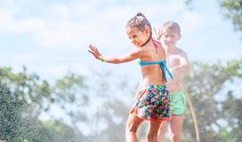 Sister and Brother play together with watering hose in garden royalty free stock image