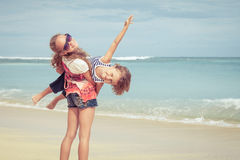 Sister and brother playing on the beach at the day time. Royalty Free Stock Photo