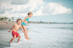 Sister and brother playing on the beach at the day time. Royalty Free Stock Photos