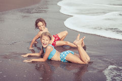 Sister and brother playing on the beach at the day time. Royalty Free Stock Images